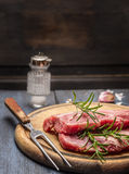 Raw pork with rosemary on a wooden board with a fork, close up. Raw pork with rosemary on wooden board with a fork, close up royalty free stock image