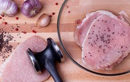 Raw pork schnitzel with meat tenderizer on wooden. Raw pork schnitzel, garlic, pink pepper and seeds of brown Indian mustard on wooden board with meat tenderizer Royalty Free Stock Images