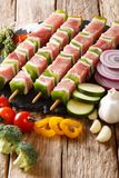 Raw pork shish kebab with pepper on skewers close-up and ingredients, vegetables, herbs. vertical. Raw pork shish kebab with pepper on skewers close-up and royalty free stock photo