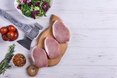 Raw pork slice. With spice and herbs on white background Stock Images