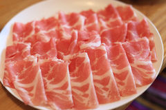Raw pork sliced in white dish for shabushabu, Japanese recipe.  Royalty Free Stock Photos