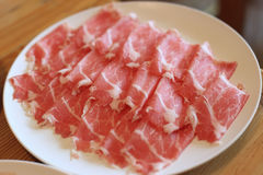 Raw pork sliced in white dish for shabushabu, Japanese recipe.  Royalty Free Stock Image
