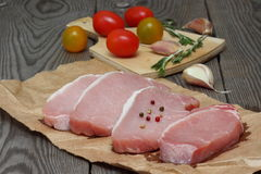 Raw pork with spices. Still life with raw pork meat and fresh vegetables royalty free stock photography