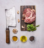 Raw pork steak on a cutting board and vintage meat cleaver with spices, garlic and herbs on wooden rustic background top view clos. Raw pork steak a cutting stock image