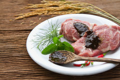 Raw pork steak  with green stuff and red chili. Black pepper sauce on  plate.(select focus at meat Stock Image