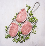 Raw pork steak on the grill for cooking over a fire with spinach wooden rustic background top view Royalty Free Stock Photos