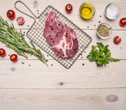 Raw pork steak on the grill for cooking with rosemary, cherry tomatoes and spices, whole pepper border ,place text  on wooden Stock Photography