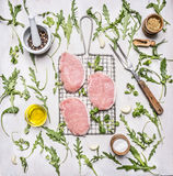 Raw pork steak on the grill for grilling with herbs, oil and spices wooden rustic background top view Royalty Free Stock Photo