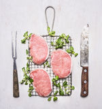 Raw pork steak on the grill with spinach and vintage knife and fork wooden rustic background top view Stock Photos