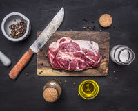 Raw pork steak with herbs, oil knife for meat on a cutting board on wooden rustic background top view close up Stock Photo