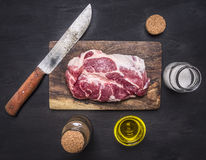 Raw pork steak with herbs, oil knife for meat on a cutting board wooden rustic background top view close up Royalty Free Stock Photo