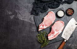 Raw pork steak. Raw pork meat with herbs, oil and spices on dark background. . Top view Stock Photography