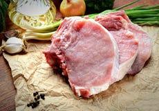 Raw pork steak, onion, garlic, pepper on brown paper Stock Image