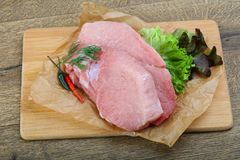 Raw pork steak. With dill and pepper ready for cooking stock image