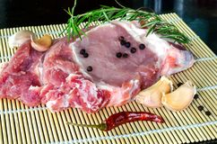 Raw pork steak ready for cooking with chili and rosemary Stock Image