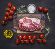 Raw pork steak with spices, butter, cherry tomatoes on a branch on wooden rustic background top view close up Royalty Free Stock Image