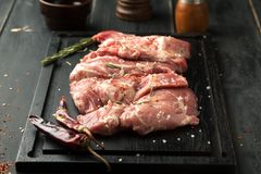 Raw pork steak with spices and rosemary. On a dark background Royalty Free Stock Photos