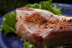Raw pork steak sprinkled with pepper on blue plate with salad Royalty Free Stock Photography