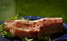 Raw pork steak sprinkled with pepper on blue plate with salad Royalty Free Stock Images