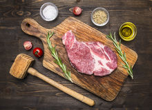 Raw pork steak on vintage cutting board with rosemary,  wooden hammer for meat and spices Stock Photography