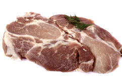 Raw pork steak on white background close-up. With a sprig of dill on top. Isolated Stock Photography