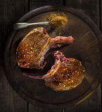 Raw pork steak on a wooden surface with aromatic spices Stock Photos