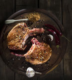 Raw pork steak on a wooden surface, a metal spoon with aromatic spices Royalty Free Stock Images