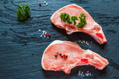 Raw pork steaks, crude cutlets with bones  and fresh parsley on black stone background.  Stock Images