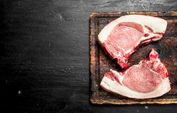 Raw pork steaks on a cutting Board. On the black chalkboard Stock Images