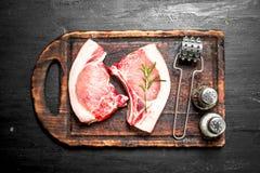 Raw pork steaks on a cutting Board. On the black chalkboard Royalty Free Stock Photos