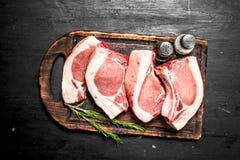 Raw pork steaks on a cutting Board. On the black chalkboard Stock Photos