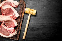 Raw pork steaks on a cutting Board. On the black chalkboard Royalty Free Stock Images