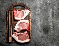 Raw pork steaks on a cutting Board. On rustic background Stock Photos