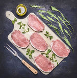 Raw pork steaks for grilling, with herbs, butter and meat fork, on a cutting board wooden rustic background top view close up Stock Photos
