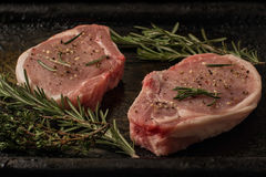 Raw pork steaks on the old iron tray Stock Image