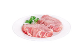 Raw pork steaks on plate. Royalty Free Stock Image