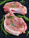Raw pork steaks with rosemary on black stone background.  Stock Photography