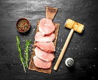 Raw pork steaks with spices and herbs. On the black chalkboard Royalty Free Stock Images
