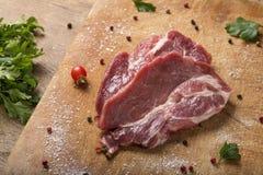 Raw pork steaks on wooden board Royalty Free Stock Image
