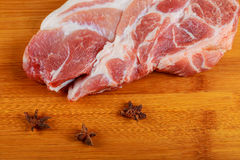 Raw pork steaks on wooden board with herbs Stock Photos