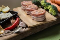 Raw pork tenderloin medallions filled with chorizo sausage and wrapped with bacon. Arranged nicely with vegetables, cheese, Chili, garlic and onions on wooden Royalty Free Stock Photo
