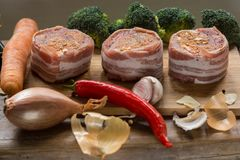 Raw pork tenderloin medallions filled with chorizo sausage and wrapped with bacon. Arranged nicely with vegetables, cheese, Chili, garlic and onions on wooden Stock Image