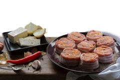 Raw pork tenderloin medallions filled with chorizo sausage and wrapped with bacon. Arranged nicely with vegetables, cheese, Chili, garlic and onions on wooden Royalty Free Stock Photos