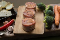 Raw pork tenderloin medallions filled with chorizo sausage and wrapped with bacon. Arranged nicely with vegetables, cheese, Chili, garlic and onions on wooden Royalty Free Stock Image