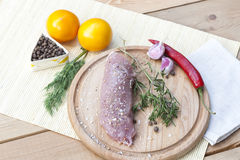 Raw pork tenderloin with spices on a wooden board. Selective focus Royalty Free Stock Photos