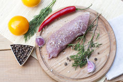 Raw pork tenderloin with spices on a wooden board. Selective focus Stock Photo