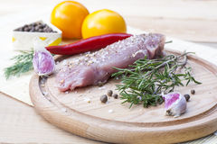 Raw pork tenderloin with spices on a wooden board. Selective focus Stock Image