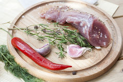 Raw pork tenderloin with spices on a wooden board. Selective focus Stock Photography