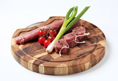 Raw pork tenderloin and vegetables. On a cutting board Royalty Free Stock Photography
