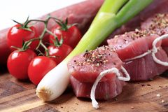 Raw pork tenderloin and vegetables. On a cutting board Royalty Free Stock Image